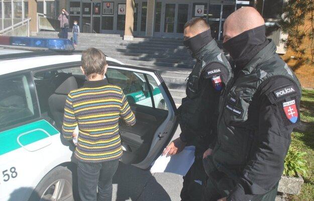 Policajti odvádzajú obvinenú do väznice na Floriánskej ulici.