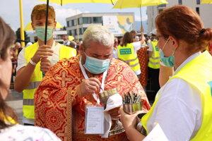 Kňazi rozdávajú sväté prijímanie.