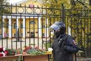 Hliadkujúci policajt pri kvetoch pre obete streľby na štátnej univerzite v Perme.