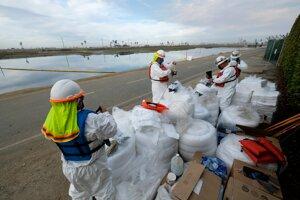 Pracovníci stavajúci bariéry na zadržanie ropy.