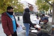 Tomáš Auxt dáva mužovi bez domova potravinový balíček, vľavo je študent Viktor Prešinský.