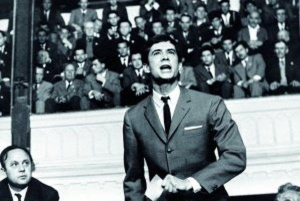 Antony Perkins ako Josef K. v slávnej scéne počas výsluchu v hale predmestskej budovy pred obrovským davom neznámych ľudí.