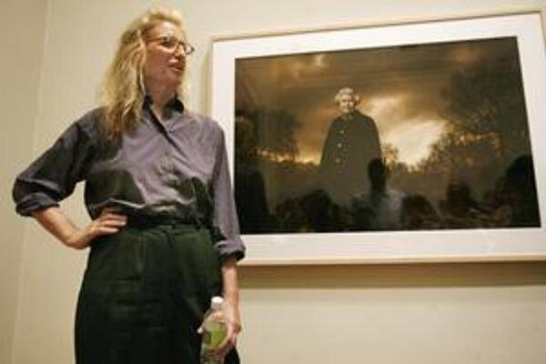 Slávna fotografka pred portrétom britskej kráľovnej.