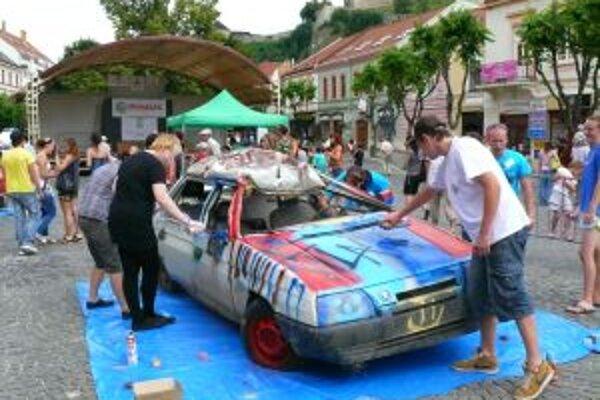 Družstvo juniorov vytvára grafiti na jednej z dvoch vrakov áut.