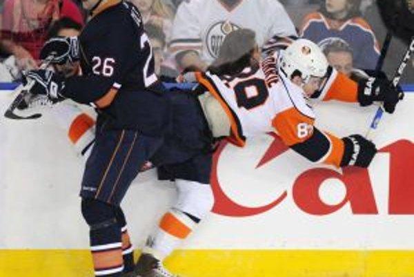 Krídelník Edmontonu Oilers Erik Cole (26) v súboji s centrom New York Islanders Mikom Comriem (89).