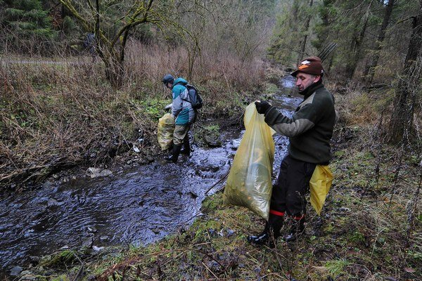 Pracovník Správy Národného parku Slovenský raj ukladá odpad z Trsteného potoka do plastového vreca počas čistenia bývalej rómskej osady.