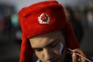 Ruský fanúšik so sovietským znakom na čiapke a ruskou trikolórou na lícach.