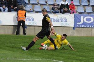 Hráč Michaloviec Stanislav Danko (vpravo) sa sklzom pokúša vypichnúť loptu Pavlovi Majerníkovi zo Skalice.