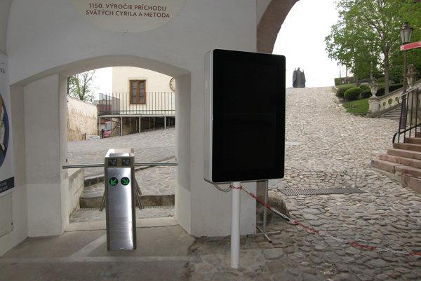 Pred vstupom do hradného areálu stojí infokiosk a turniket.