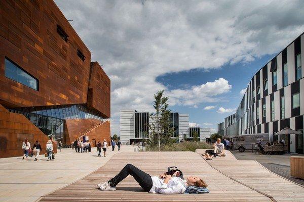 V hnedej budove sú učebne, na zemi študenti.