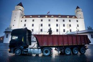 Popred sochu Svätopluka jazdia veľké nákladné autá.