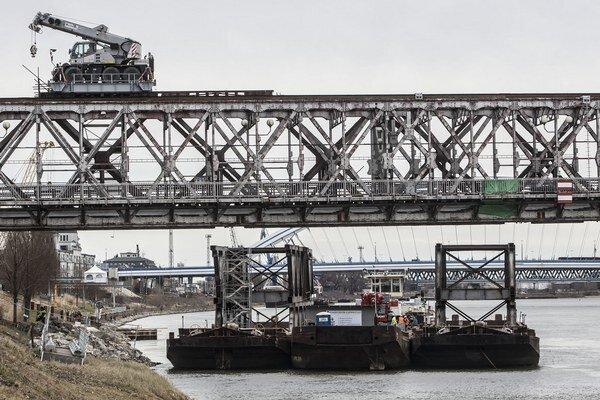 Jeden žeriav je na moste, druhý na lodi.