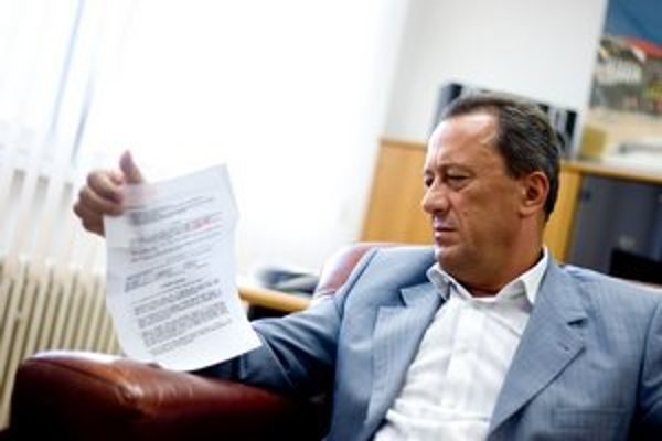 Ľubomír Belfi si prezerá dodatok k zmluve o strážení areálov podniku.