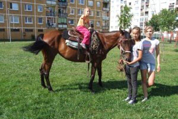 Milsy s dieťaťom na chrbte. Vedľa stojí jej majiteľka Monika (vľavo) s kamarátkou.