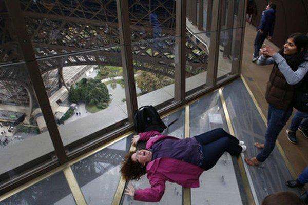 Návštevníčka leží na novej priehľadnej podlahe zo skla.