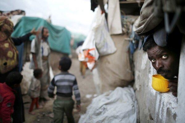 Muž sa pozerá z okna svojej chatrče v slume.