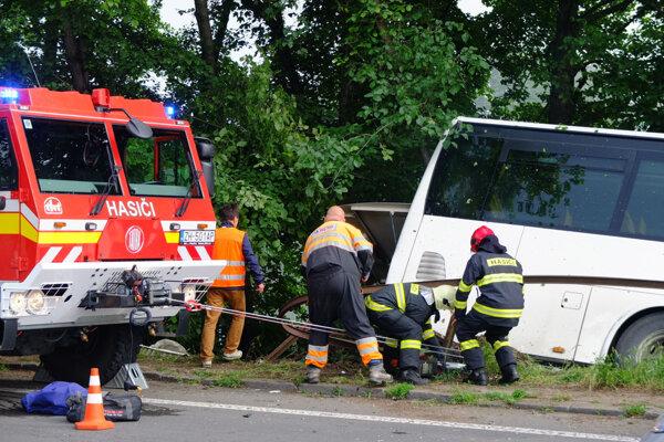 Autobus sa hasiči snažia dostať zo svahu, kde ostal zakliesnený na stromoch.