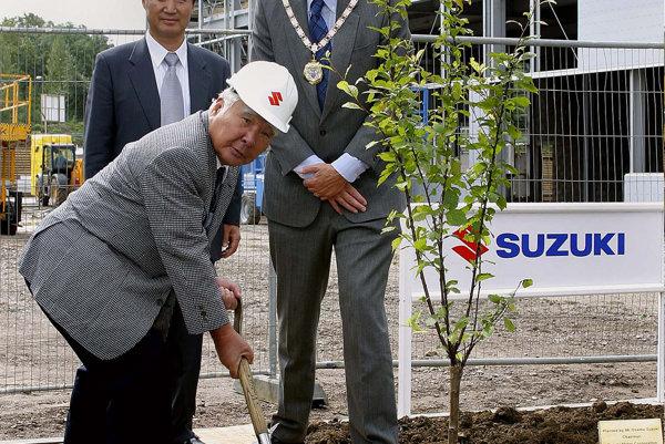 Osamu Suzuki (v prilbe) počas slávnostného otvorenia novej predajne Suzuki vo Veľkej Británii.