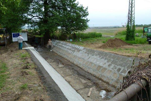 Prívodný kanál k rybníkom opravujú.