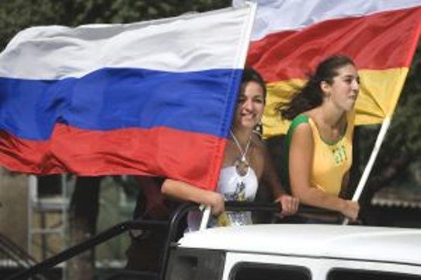 Osetky v metropole Cchinvali oslavovali s ruskou (vľavo) a osetskou vlajkou.