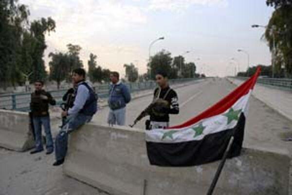 Sunitskí dobrovoľníci strážia most, ktorý oddeľuje sunitskú a šiitskú štvrť v Bagdade.