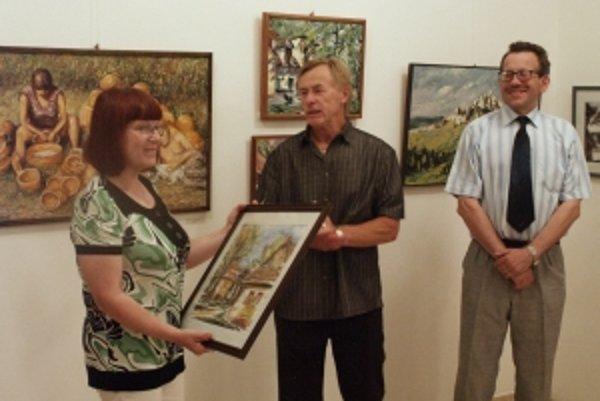 Vystavujúci výtvarník  Jozef Chrena (v strede) odovzdáva jeden zo svojich obrazov ako dar Záhorskému osvetovému stredisku v Senici do rúk riaditeľke RNDr. Ľubici Krištofovej. Vpravo kurátor výstavy PhDr. Štefan Zajíček, riaditeľ Záhorskej galérie v Senici