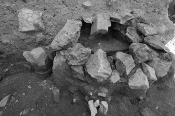 Nájdená piecka z 9. až 10. storočia a vchody do odkrytých pivníc pri hradnom brale (dole).