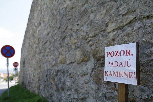 Výstražná tabuľa. Staticky je múr v poriadku, vypadávajú však z neho kamene.