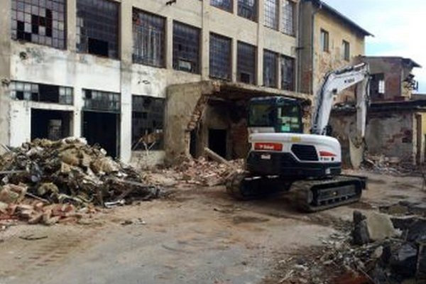 Vypratávanie sutín. Schátralé budovy demolujú robotníci.
