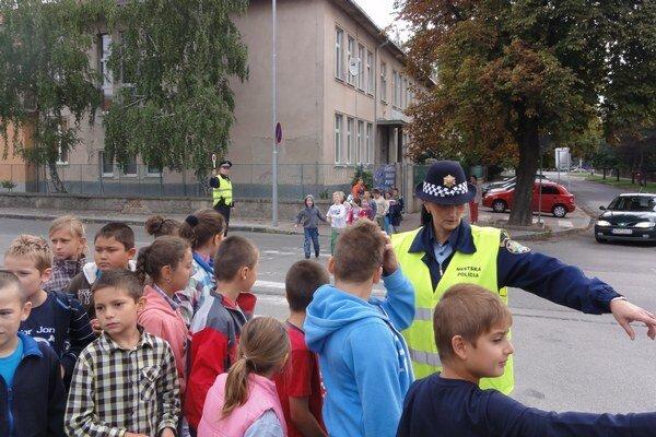 Mestskí policajti so žiakmi prechádzajú cez Gúgsku ulicu.