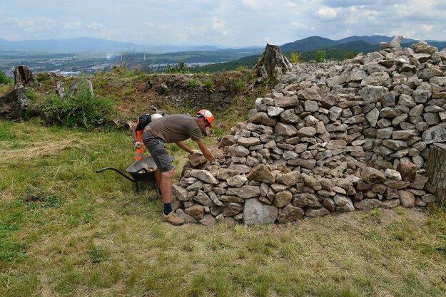 Nezamestnaní pri triedení kameňa pre stavebnú sanáciu.