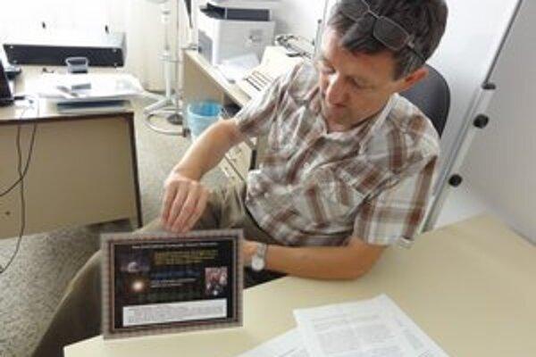 Štefan Kürti spolu s certifikátom o pomenovaní planétky.
