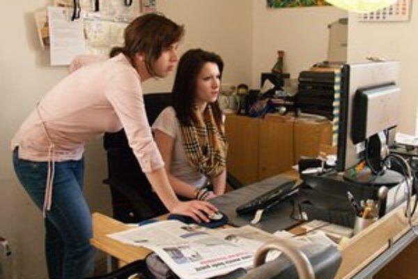 Donedávna naša grafička, dnes už učiteľka v ZŠ na Mostnej Eva Belaňová (vľavo)predstavuje Kristíne spôsob zalamovania novín.