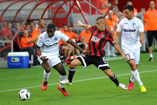 Kapitán Trnavy Martin Mikovič v súboji s dvoma protihráčmi.