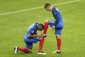 Francúz Dimitri Payet (vľavo) bozkáva kopačku spoluhráčovi Antoinovi Griezmannovi.