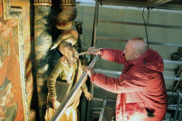 Albín Okša dokončuje obnovu oltára v Diviackej Novej Vsi.