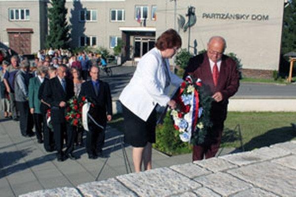 Starostka Malinovej Mária Luprichová (vľavo) a poslanec obecného zastupiteľstva Jozef Patorek kladú veniec k pamätníku.