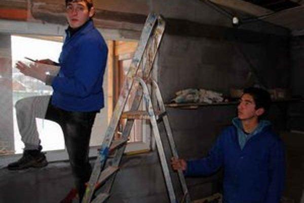 Mladí Rómovia. Prácam sa učia v malom domčeku. Aby v ňom mali teplo, nachystajú tiež drevo a zakúria si.