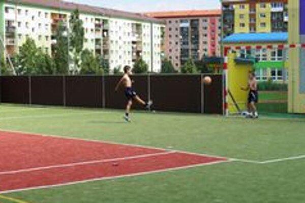 Chlapci na multifunkčnom ihrisku s umelou trávou pri ZŠ Komenského počas dňa hrajú futbal.