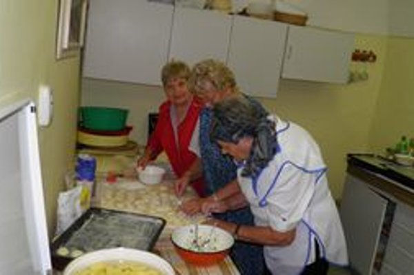 Piekli už aj pre radošincov. Tri gazdinky vypekajú koláčiky z kysnutého cesta. Vedúca klubu pri MsÚ Margita Kissová (vpredu).