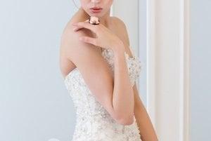 Rozprávková: Korzetové svetlé šaty so srdiečkovým korzetom a kvetovou sukňou s vlečkou sa postarajú o to, aby ste vyzerali božsky. Briliantový prsteň s ružovým koralom je skvelou bodkou rozprávkovej svadby.