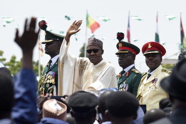 Prezident Muhammad Buhari (v strede) kýve ľuďom počas svojej inaugurácie.