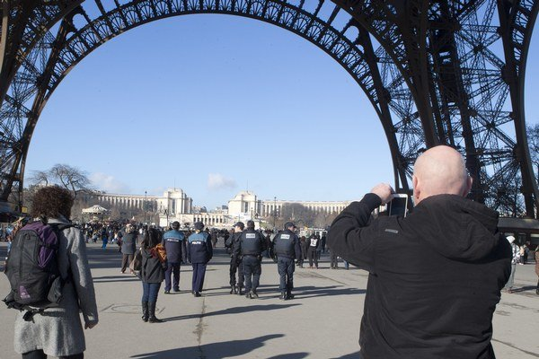 Turista pod Eiffelovou vežou v Paríži.