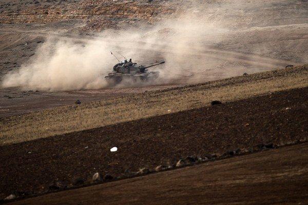 Turecký tank jazdí na kopci s výhľadom na sýrske mesto Kobané.
