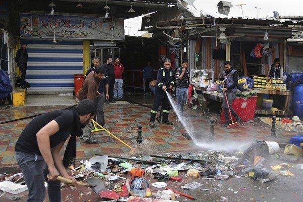 Iračan čistí ulicu po bombovom útoku.