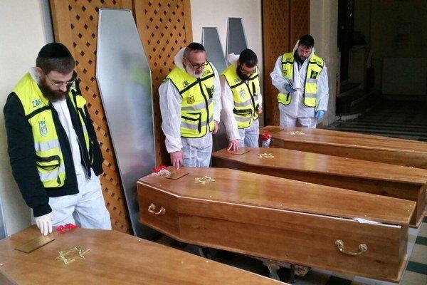 Dobrovoľníci recitujú modlitby nad rakvami s telesnými pozostatkami štyroch zastrelených rukojemníkov, ktorých zabili pri teroristickom útoku v kóšer potravinách, po prípravách na ich pohreb v Paríži.