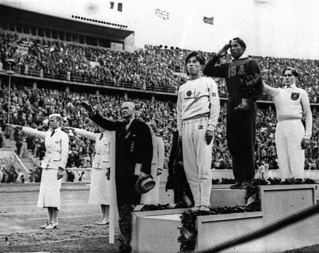 Jesse Owens (na stupni víťazov v strede).