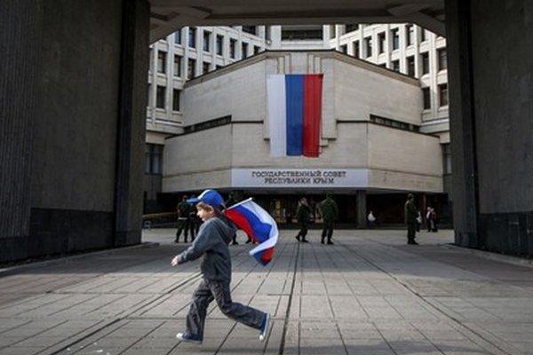 Chlapec uteká s ruskou vlajkou pred krymským parlamentom v Simferopoli.