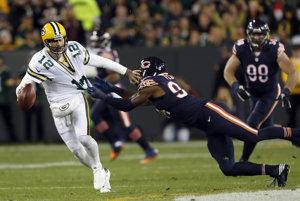 Hviezdneho quarterbacka tímu Green Bay Packers Aarona Rodgersa (vľavo) sa pokúša zložiť na zem hráč Chicaga Bears Leonard Floyd.