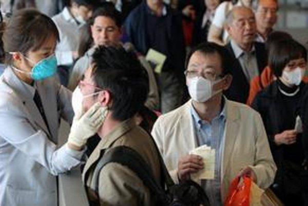 Juhokórejská karanténna zdravotníčka (vľavo) kontroluje teplotu japonskému pasažierovi proti eventuálnej infekčnej nákazy prasacou chrípkou.